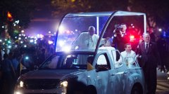 Pope Francis waves to well-wishers as he arrives at where he will be staying in Manila on January 15, 2015. (AFP Photo/Johannes Eisele)